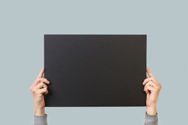 Frauenhände, die ein leeres schwarzes papier halten