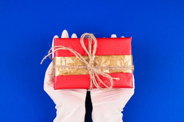 Frauenhände, die ein rotes geschenk halten