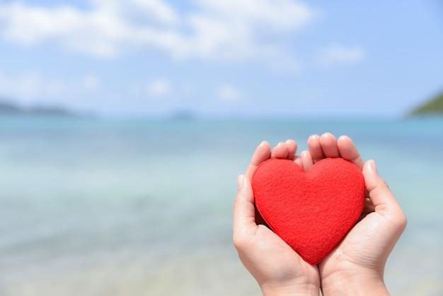 Frauenhände, die ein rotes herz auf dem strand mit unscharfem hintergrund des meeres und des blauen himmels halten. liebe konzept.