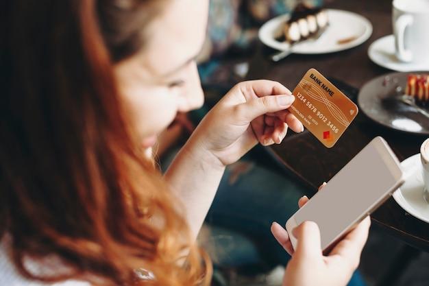 Frauenhände, die ein smartphone und eine goldene kreditkarte für online-transaktion verwenden, während sie einen schreibtisch sitzen.
