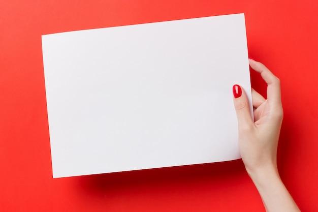 Frauenhände, die ein weiß ein leeres papier a4 auf einem roten hintergrund halten