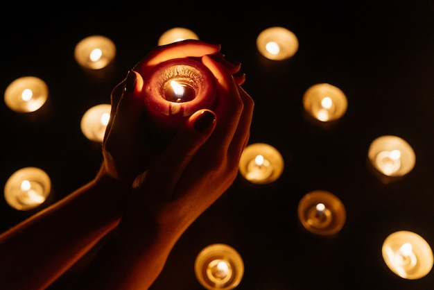 Frauenhände, die eine brennende kerze halten. viele kerzenflammen leuchten. nahansicht.