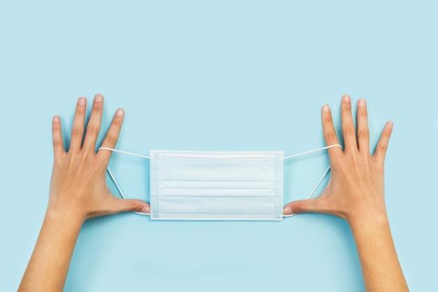 Frauenhände, die eine chirurgische maske auf einem hellblauen hintergrund in einer draufsicht halten