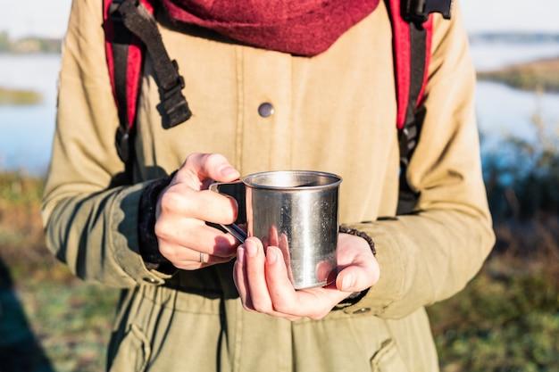 Frauenhände, die eine dampfende tasse in der schönen naturumgebung halten. genießen sie einen kaffee in einer touristischen metallschale auf einer wanderung