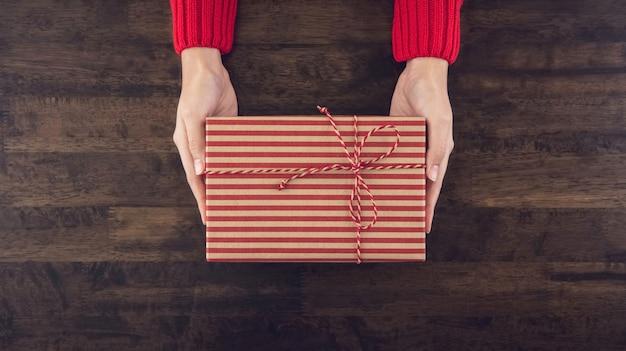 Frauenhände, die eine draufsicht der christsmas geschenkbox über hölzerne tabelle geben