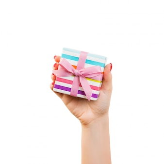 Frauenhände, die eine eingewickelte geschenkbox halten