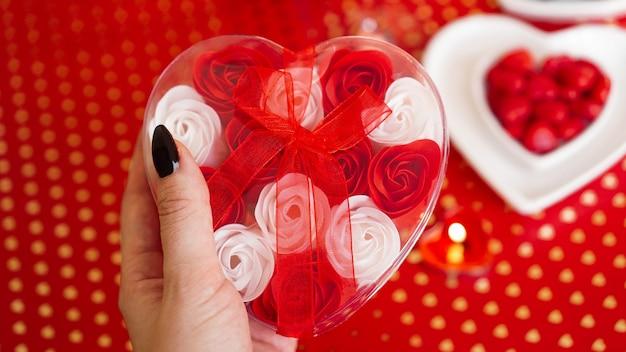 Frauenhände, die eine geschenkbox in herzform mit schönen rosen über rotem fest halten. konzept des schenkens an valentinstagferien