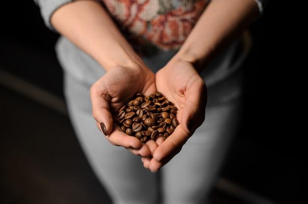 Frauenhände, die eine handvoll frische kaffeebohnen halten