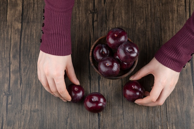 Frauenhände, die eine hölzerne schüssel mit gesunden purpurroten pflaumen halten