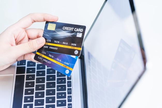 Frauenhände, die eine kreditkarte für online-einkauf halten
