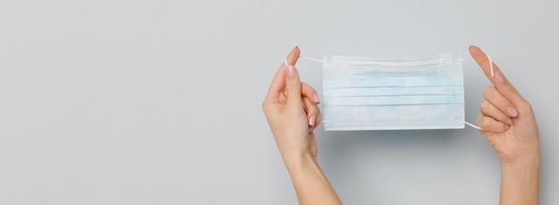 Frauenhände, die eine medizinische gesichtsmaske halten, schutz gegen allergie, virus, covid-19 und coronavirus.