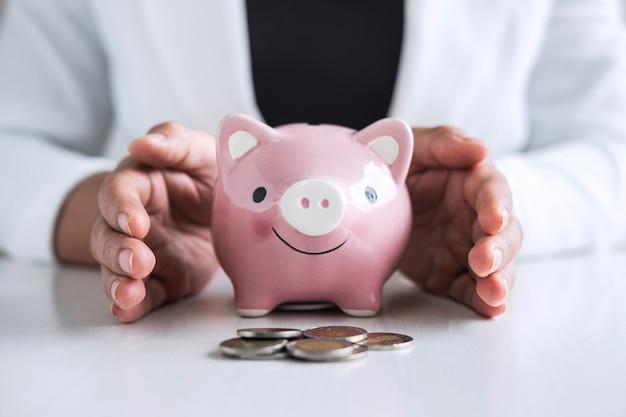 Frauenhände, die eine schützende geste eines sparschweins für die planung haben, steigern das wachsen, um zu profitieren