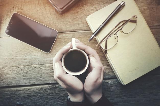 Frauenhände, die eine tasse kaffee mit arbeitstisch halten