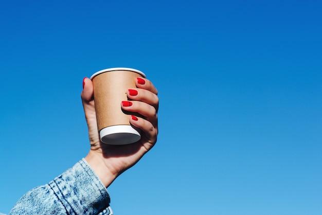 Frauenhände, die eine tasse kaffee über hintergrund des blauen himmels halten. hipster-mädchen mit pappbecher mit kaffee zum mitnehmen. papierkaffeetasse in frauenhänden mit perfekter maniküre.