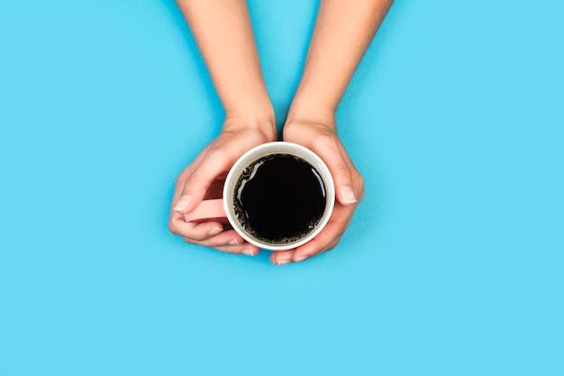 Frauenhände, die eine tasse schwarzen kaffee auf einem hellblauen hintergrund in einer draufsicht halten