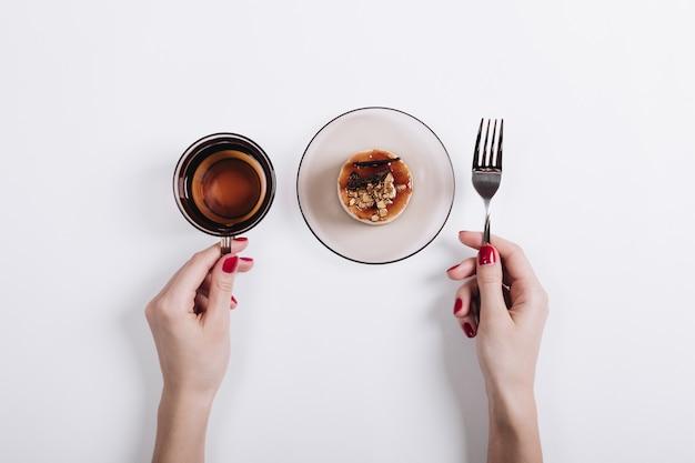 Frauenhände, die eine tasse tee und einen teller mit einem kuchen halten