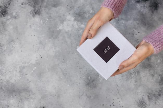 Frauenhände, die eine weiße geschenkbox mit den wörtern halten