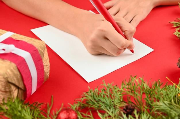 Frauenhände, die einen brief für weihnachten schreiben