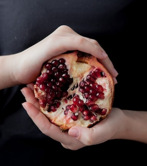 Frauenhände, die einen granatapfel auf dem schwarz halten.