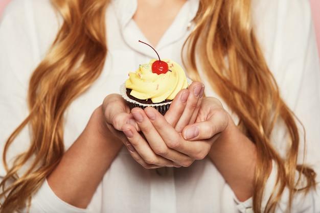 Frauenhände, die einen köstlichen leckeren kleinen kuchen halten