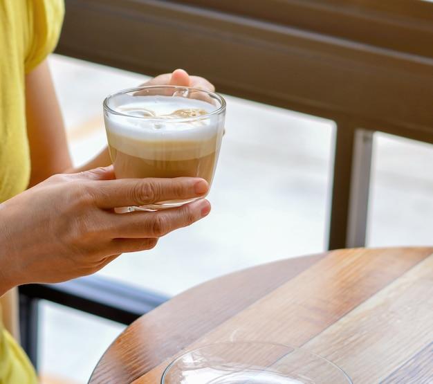 Frauenhände, die einen tasse kaffee halten.