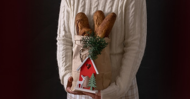 Frauenhände, die einkaufstasche mit brot für feiertags-neujahrs- oder weihnachtslieferungskonzept halten