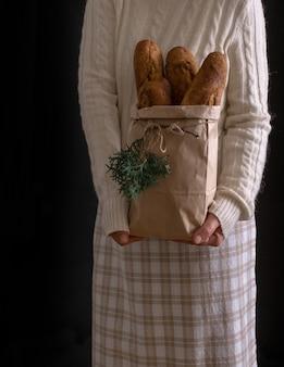 Frauenhände, die einkaufstasche mit brot halten
