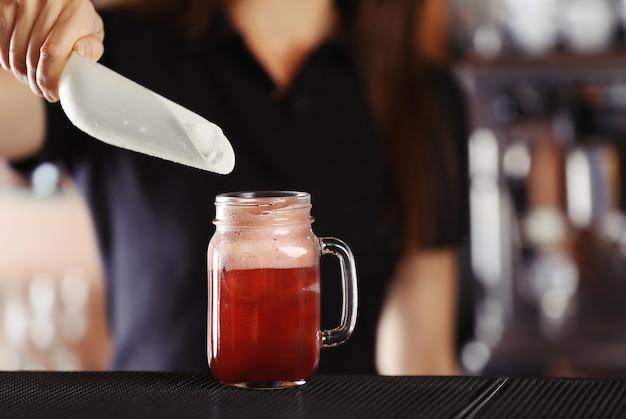 Frauenhände, die eis in cocktail auf bartheke hinzufügen