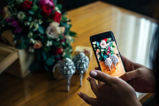 Frauenhände, die foto von hellen hochzeitsblumen und luxusschuhen mit smartphone machen.