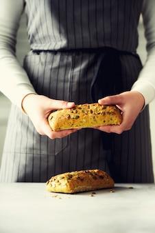 Frauenhände, die frisch gebackenes brot halten.