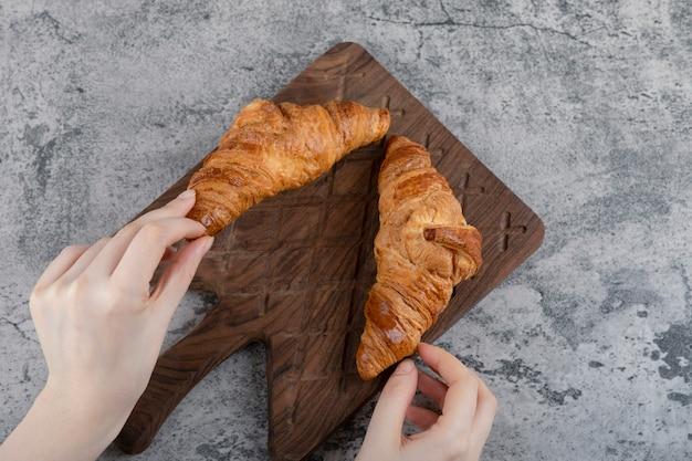 Frauenhände, die frische croissants auf einem hölzernen schneidebrett halten.