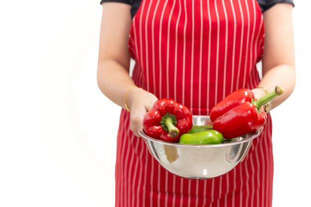 Frauenhände, die frische gemüsepaprikas in einer schüssel lokalisiert halten