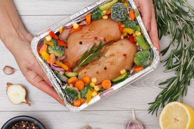 Frauenhände, die frische rohe hähnchenbrust oder filet mit gefrorenem gemüse in metallbehälter halten, bereit zum kochen im mikrowellenherd oder herd... draufsicht mit zutaten im hintergrund.