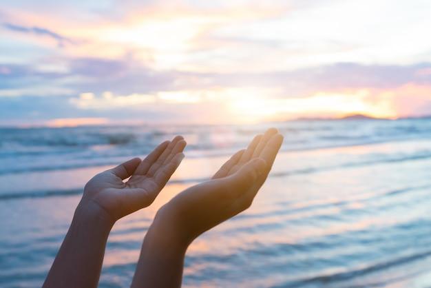 Frauenhände, die für das segnen vom gott während des sonnenunterganghintergrundes beten. hoffnungs-konzept.