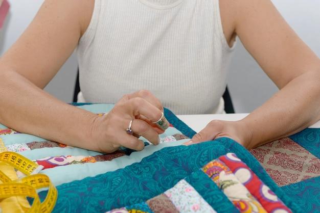 Frauenhände, die für ende eine steppdecke nähen.