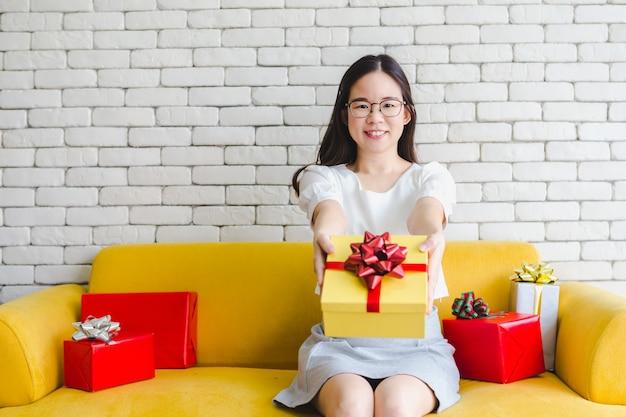 Frauenhände, die gelbes giftbox mit dem roten bogen geben geschenk halten