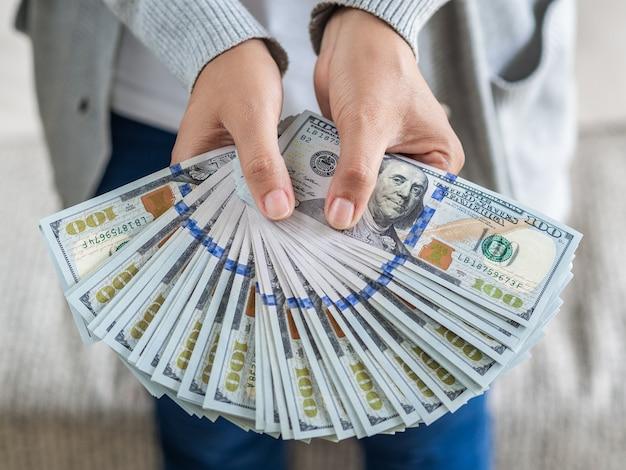 Frauenhände, die geld us-dollar rechnungen vorschlagen ihnen vor.