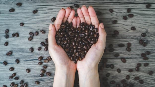 Frauenhände, die geröstete kaffeebohnen mit herzform halten