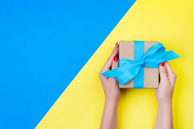 Frauenhände, die geschenk eingewickelt und mit blauem bogen auf blau und gelb verziert halten