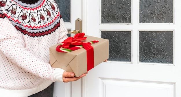 Frauenhände, die geschenk nahe weißer tür zu hause am vorabend der feiertage weihnachten und neujahr halten.