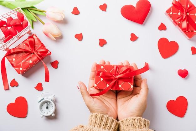 Frauenhände, die geschenk- oder geschenkbox verziert halten und rote herzüberraschung halten