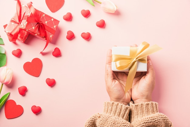 Frauenhände, die geschenk- oder geschenkbox verziert halten und rotes herz überraschen