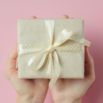 Frauenhände, die geschenkbox in den palmen auf rosa hintergrund halten