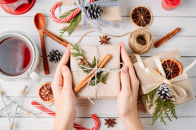 Frauenhände, die geschenkbox mit weihnachtsdekorationen auf einer weißen hölzernen, draufsicht einwickeln