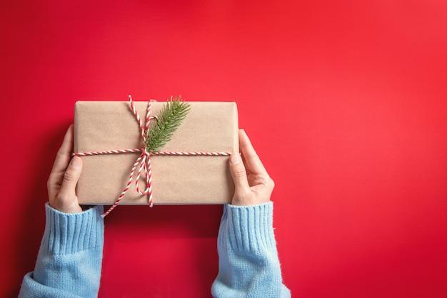 Frauenhände, die geschenkpapier-geschenkbox auf rot halten