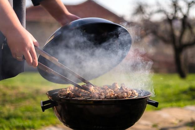 Frauenhände, die grill grillen, treffen sich auf dem grill draußen im hinterhof Premium Fotos