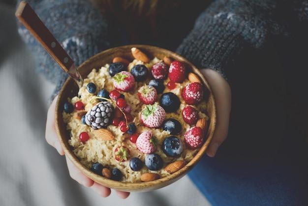 Frauenhände, die hafermehlbrei mit gefrorenen beeren, mandeln in der hölzernen schüssel halten. gesundes frühstück. sauberes essen, detox-diät. vegetarisches, rohes, veganes konzept