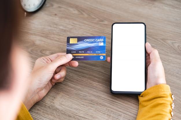 Frauenhände, die handy mit leerem bildschirm und kreditkarte auf schreibtisch halten und handy für das on-line-einkaufen, internetbanking, on-line-handel verwenden