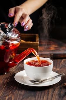 Frauenhände, die heißen tee in einer tasse vom topf gießen
