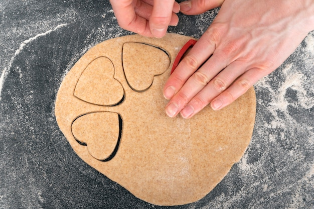 Frauenhände, die herzförmigen teig machen. prozess der herstellung von shortbread-cookies.